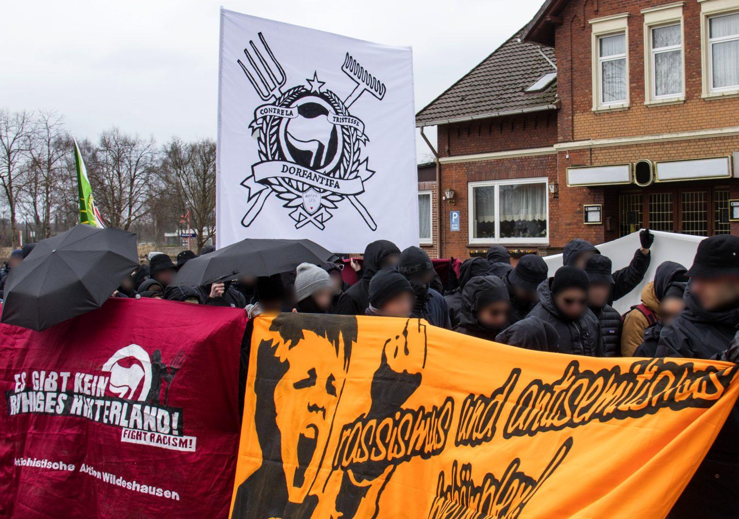 Dorfantifa-Demonstrationszug vor einer Gaststätte.