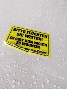 Auf gelbem Aufkleber in schwarzer Schrift steht: Bitte flüchten Sie weiter! Es gibt hier nichts zu wohnen. Refugees not welcome!