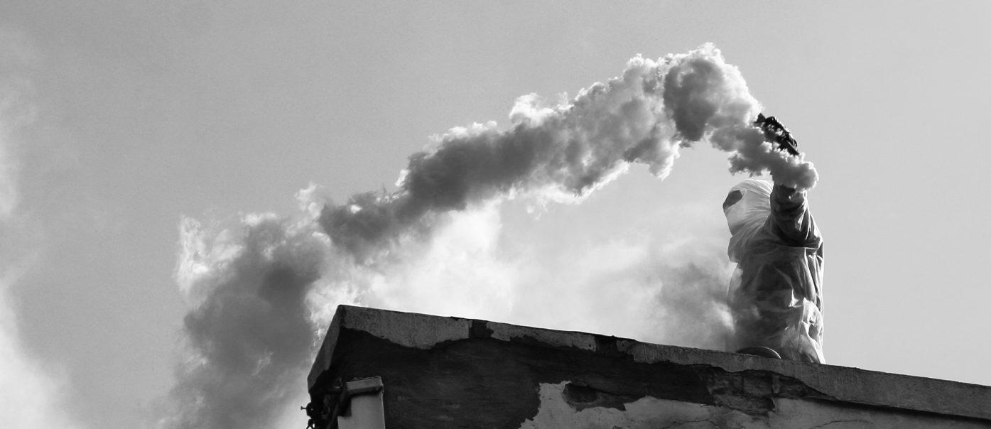 Vermummte Person mit Rauchfackel auf dem Dach eines maroden Gebäudes.
